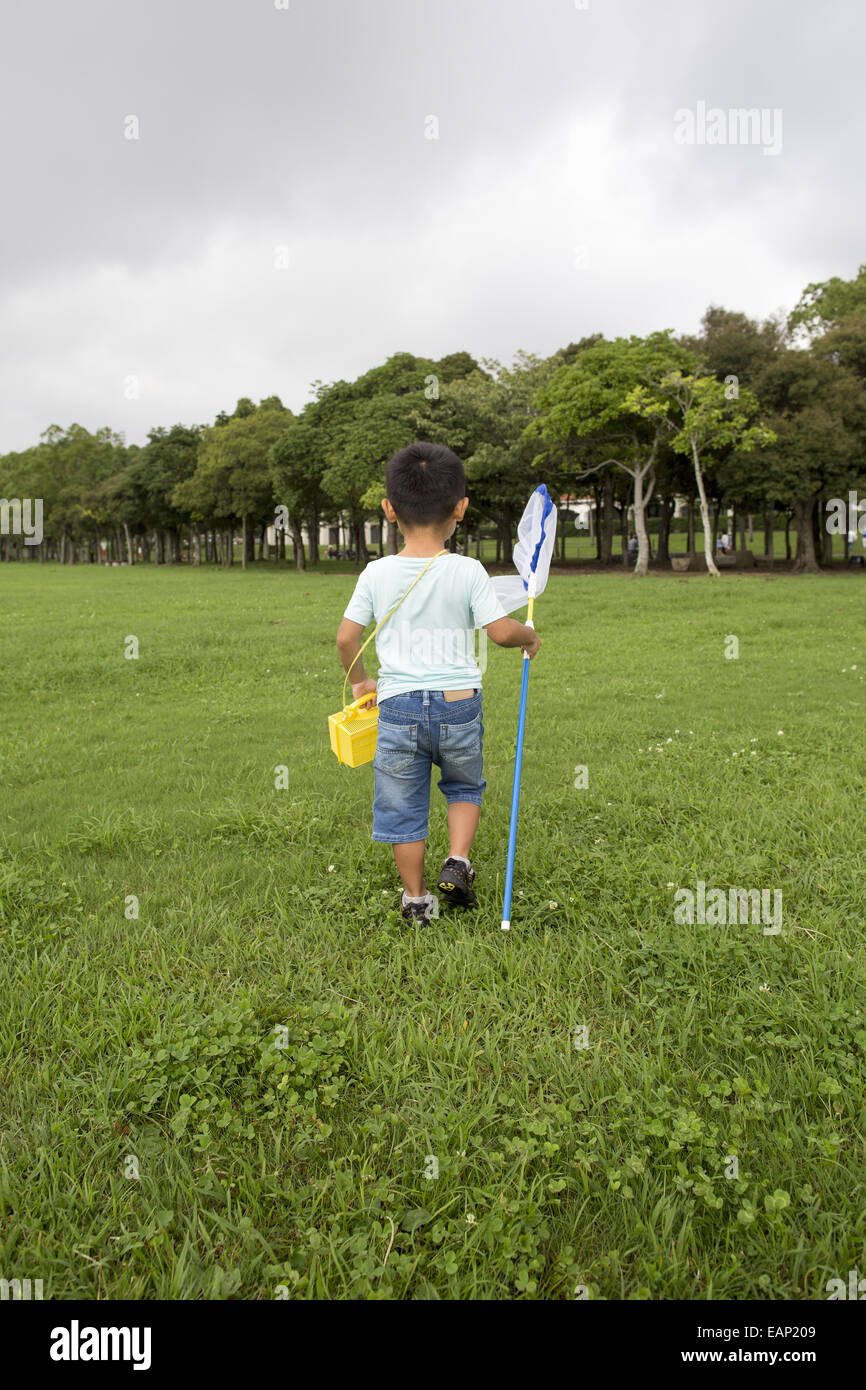 Young boy carrying a butterfly net. - Stock Image