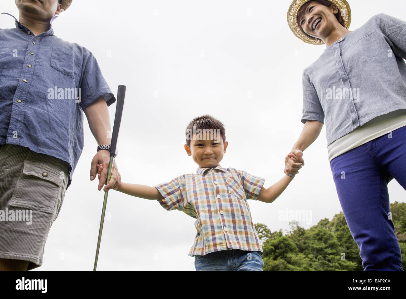 Family on a golf course. Two parents and a boy holding hands. - Stock Image