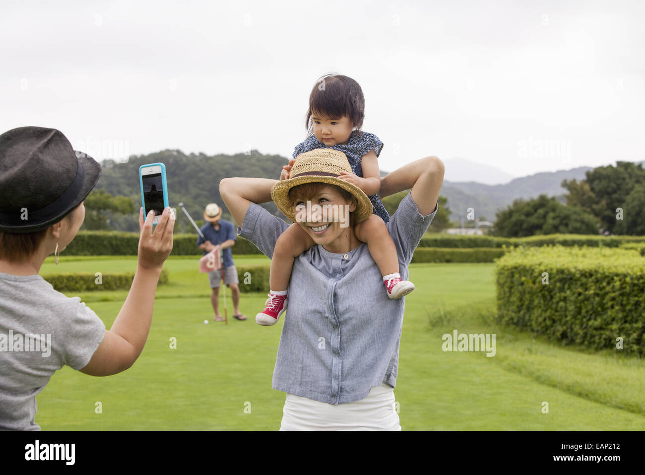 Family on a golf course. A child on a woman's shoulders. - Stock Image