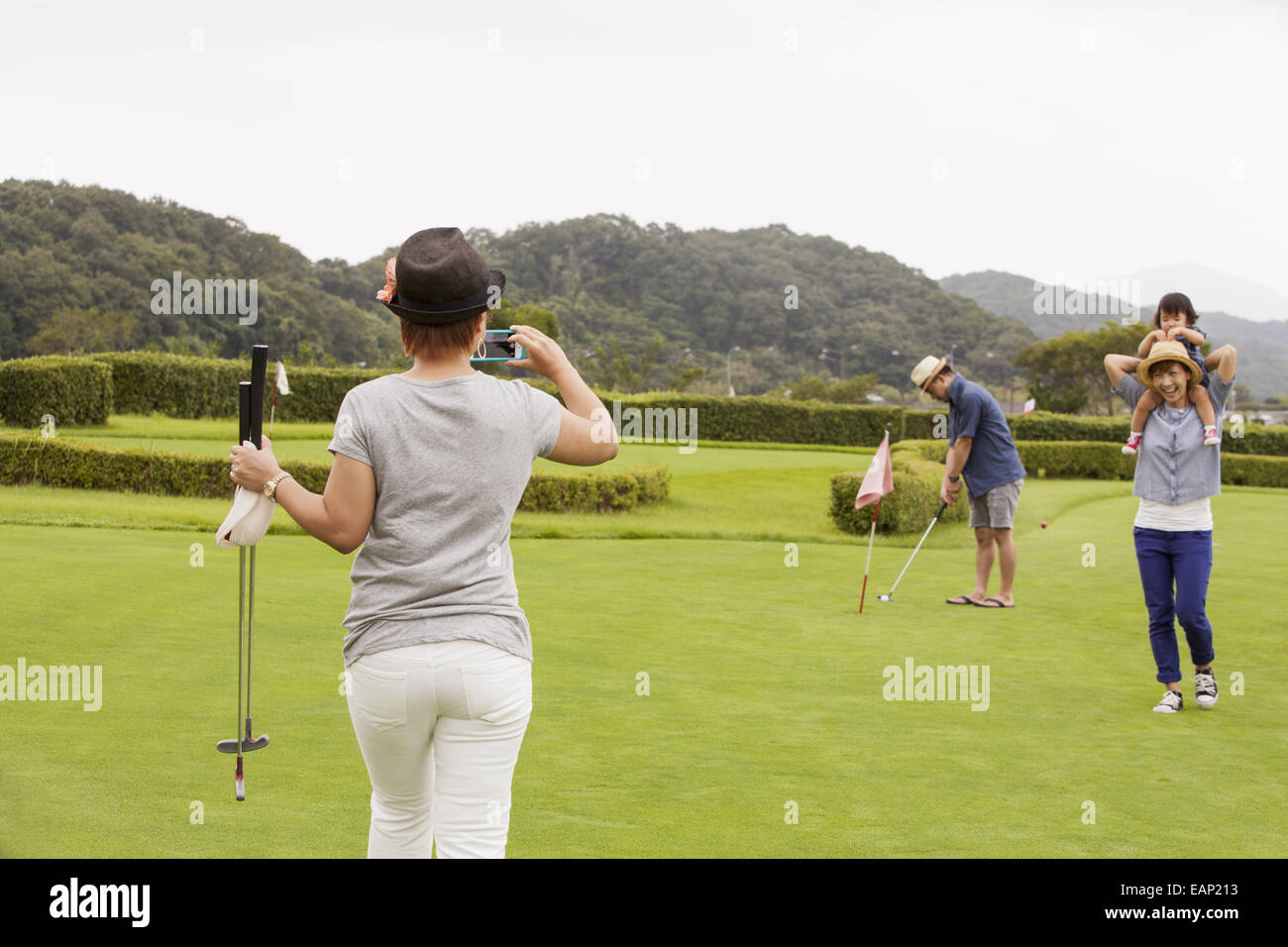 Family on a golf course.A child and three adults. a woman with a camera. - Stock Image