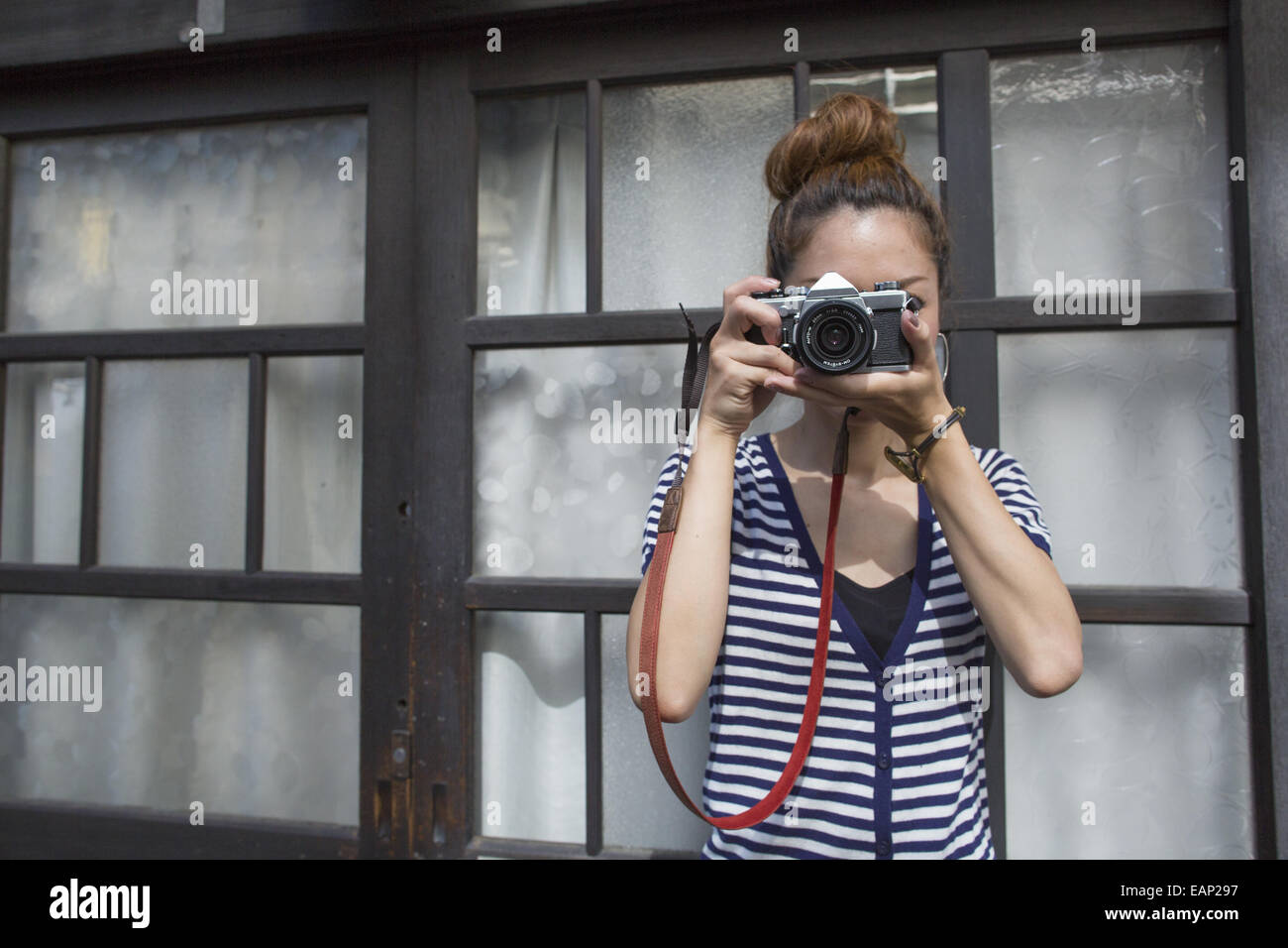 Woman standing outdoors, looking through a camera. - Stock Image