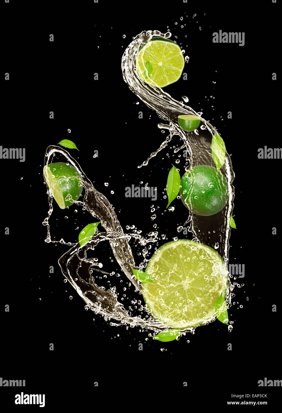 Limes in water splash, isolated on black background - Stock Image
