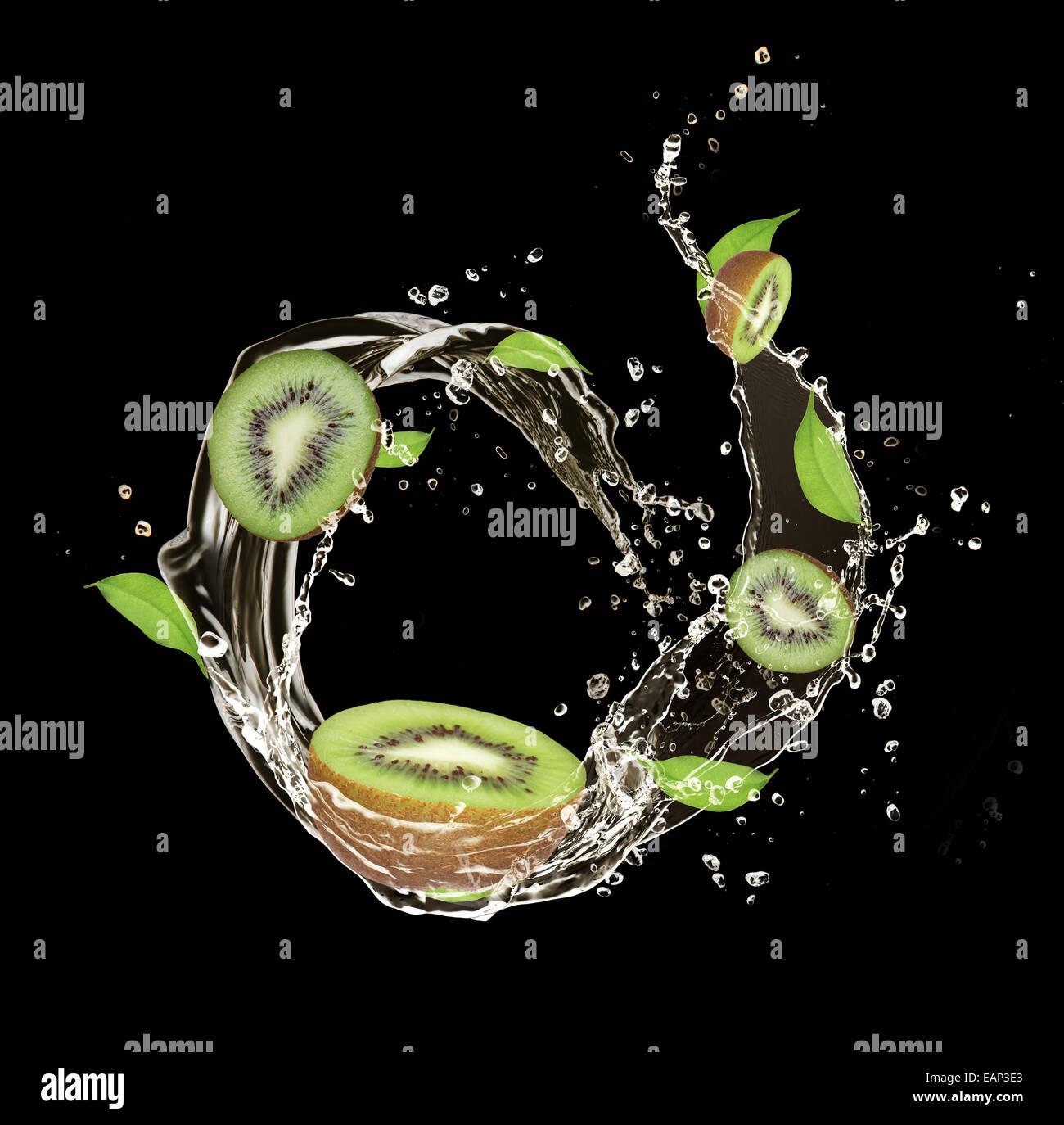 Fresh kiwi in water splash, isolated on black background - Stock Image