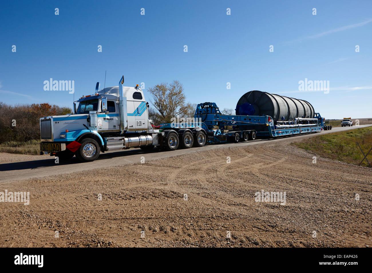 oversize load transporting a grain silo on local rural road Saskatchewan Canada - Stock Image