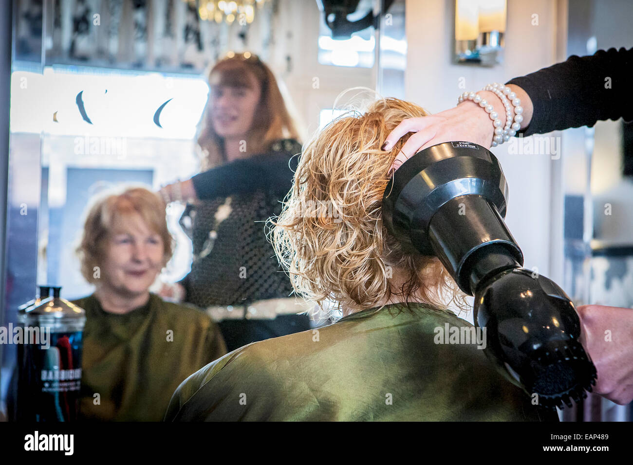 Reflection of hairdresser scrunching a blond lady's hair Stock Photo