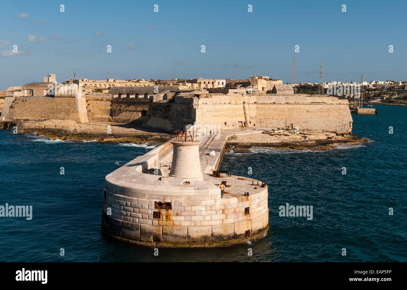 Valletta, Malta - entrance to the Grand Harbour. The Ricasoli lighthouse and breakwater with Fort Ricasoli (Forti - Stock Image