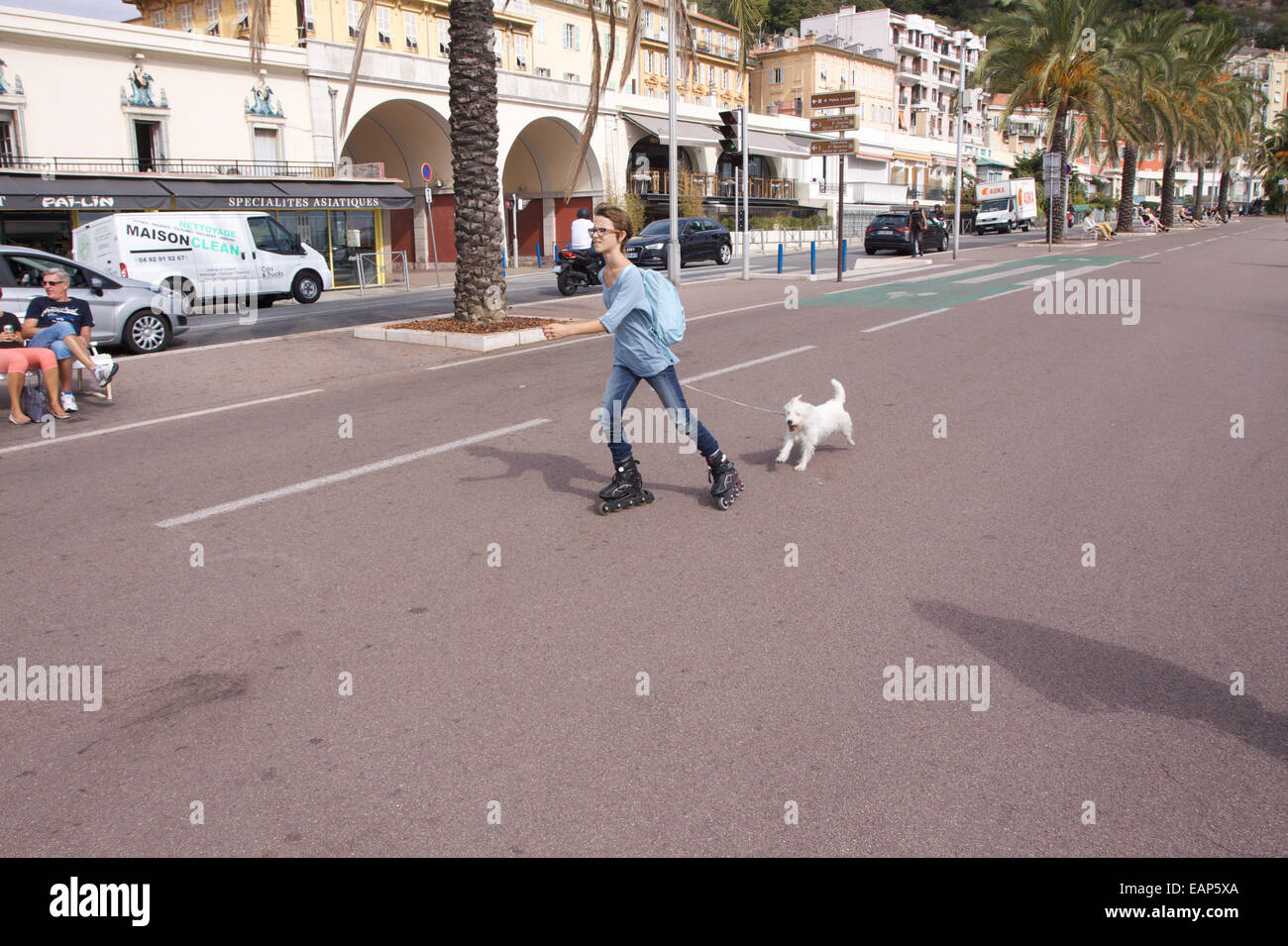 A lady rollerblading with her dog on the seafront in Nice, South of France - Stock Image