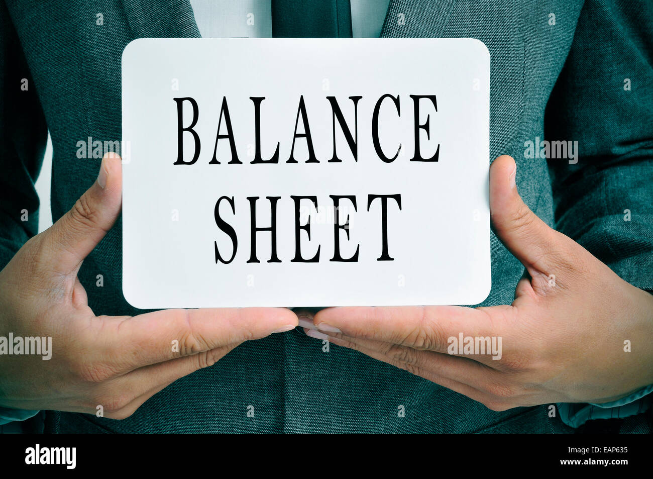 a businessman showing a signboard with the text balance sheet written in it Stock Photo
