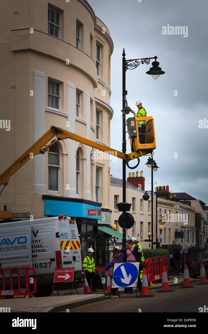 Workman on cherry picker lift maintaining street light Stock Photo