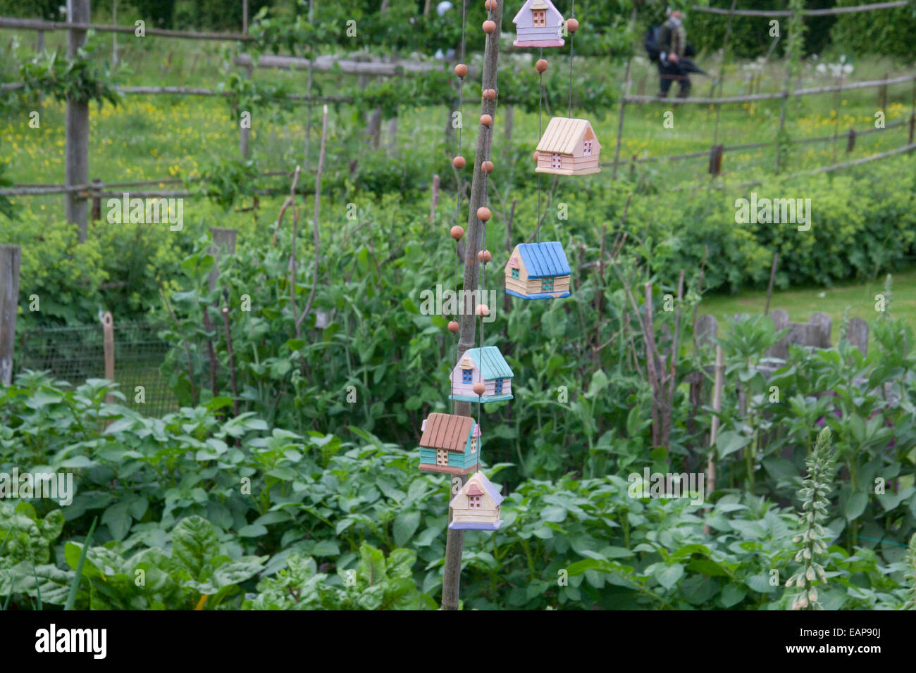 Garden decorations hanging from a pole in a rustic vegetable plot at ...