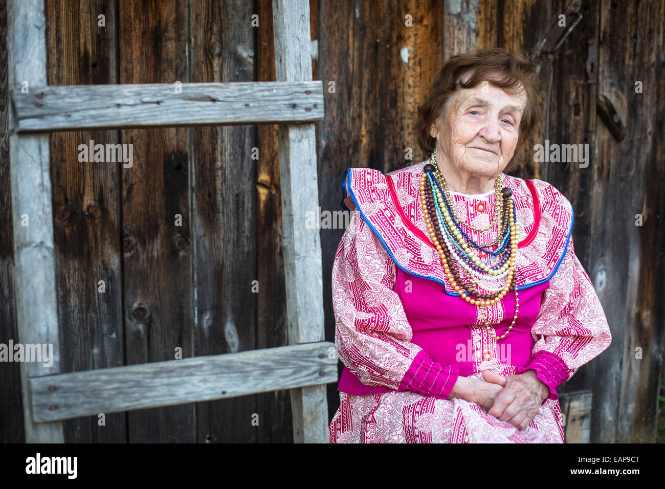 Old woman in ethnic red and white dress and necklace, outdoors in the village. - Stock Image