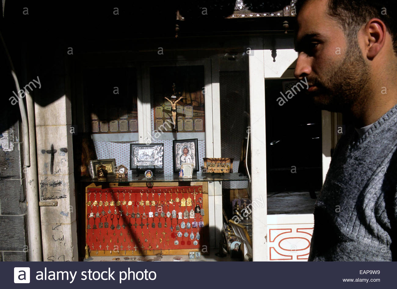 A man near a shop offering religious items, Damascus catholic district, Syria. - Stock Image