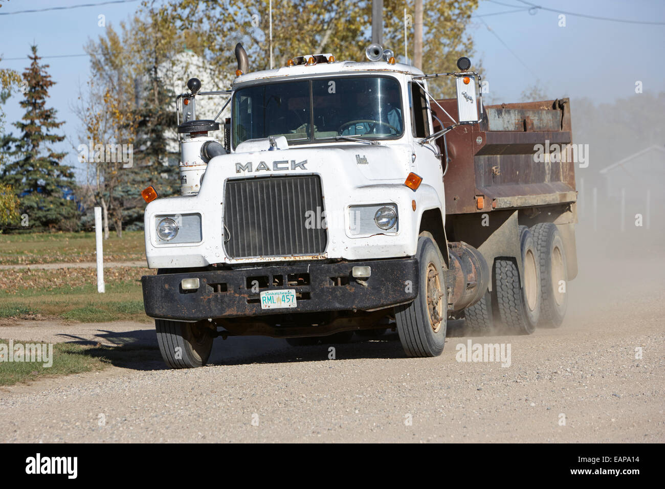 mack truck driving down rough unpaved rural road in farming community Saskatchewan Canada - Stock Image