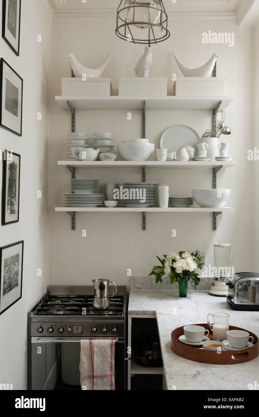 white crockery on open shelving in galley style kitchen with marble surfaces - Galley Style Kitchen