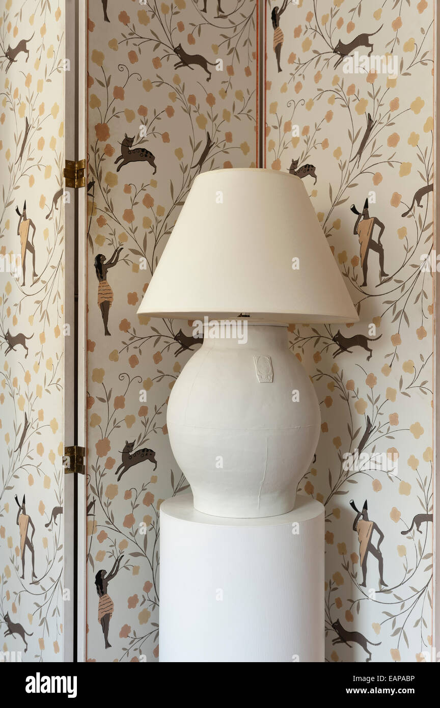 Ceramic lamp on plinth in front of a folding screen covered in wallpaper by Marie Laurencin - Stock Image