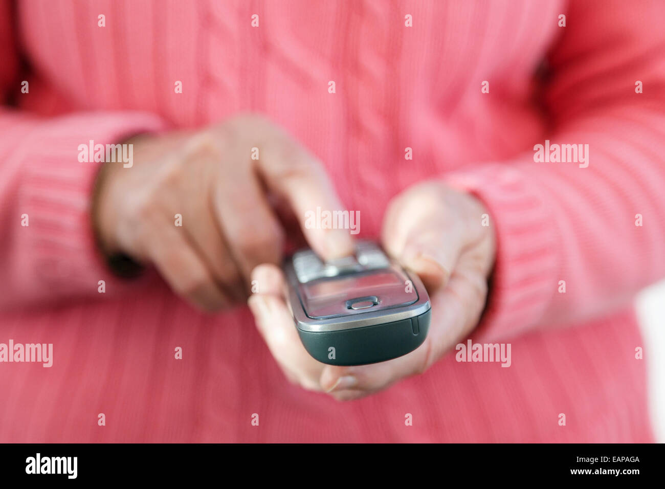 A right-handed senior woman using a touch phone handset keypad to dial a telephone number to make a phone call from - Stock Image