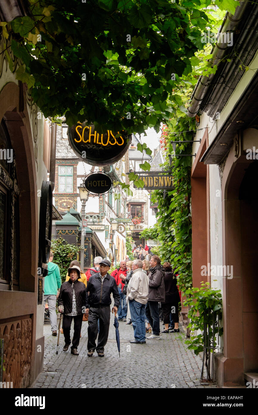Tourists in famous popular narrow cobbled Drosselgasse street in old winegrowing town of Rüdesheim am Rhein, - Stock Image