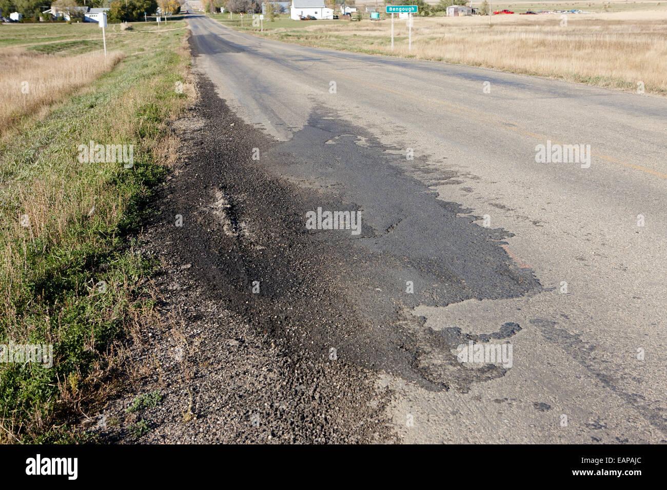 patched piece of damaged tarmac highway Saskatchewan Canada - Stock Image