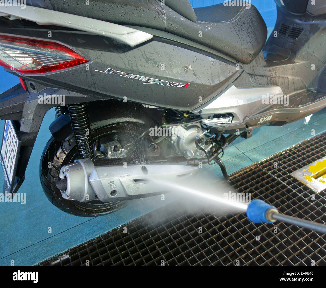 Cleaning a bike with high pressure pump at sel.service station in Spain. - Stock Image