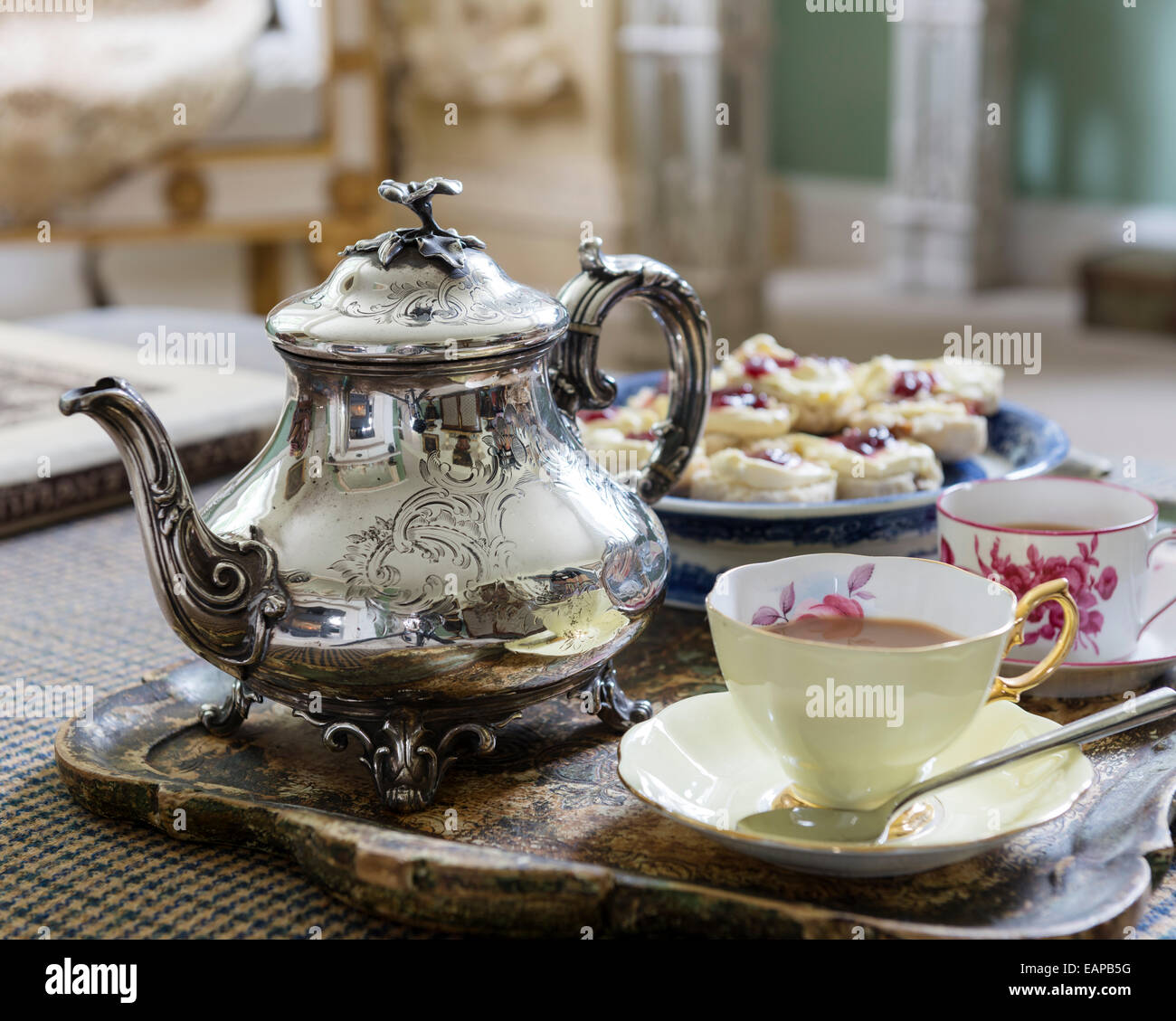 Silver teapot on tray with cups and saucers and scones - Stock Image