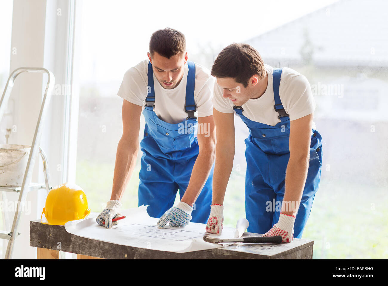 Builders house meeting stock photos builders house meeting stock group of builders with blueprint stock image malvernweather Image collections