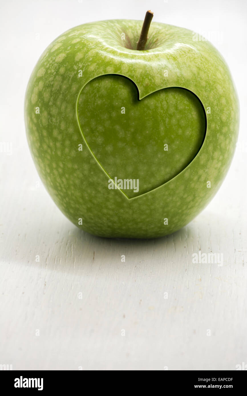 Green apple with carved heart, conceptual health and wellness - Stock Image