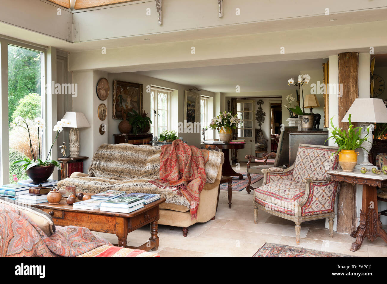 Open plan living room filled with antique seating upholstered in a variety of textiles and fabrics - Stock Image