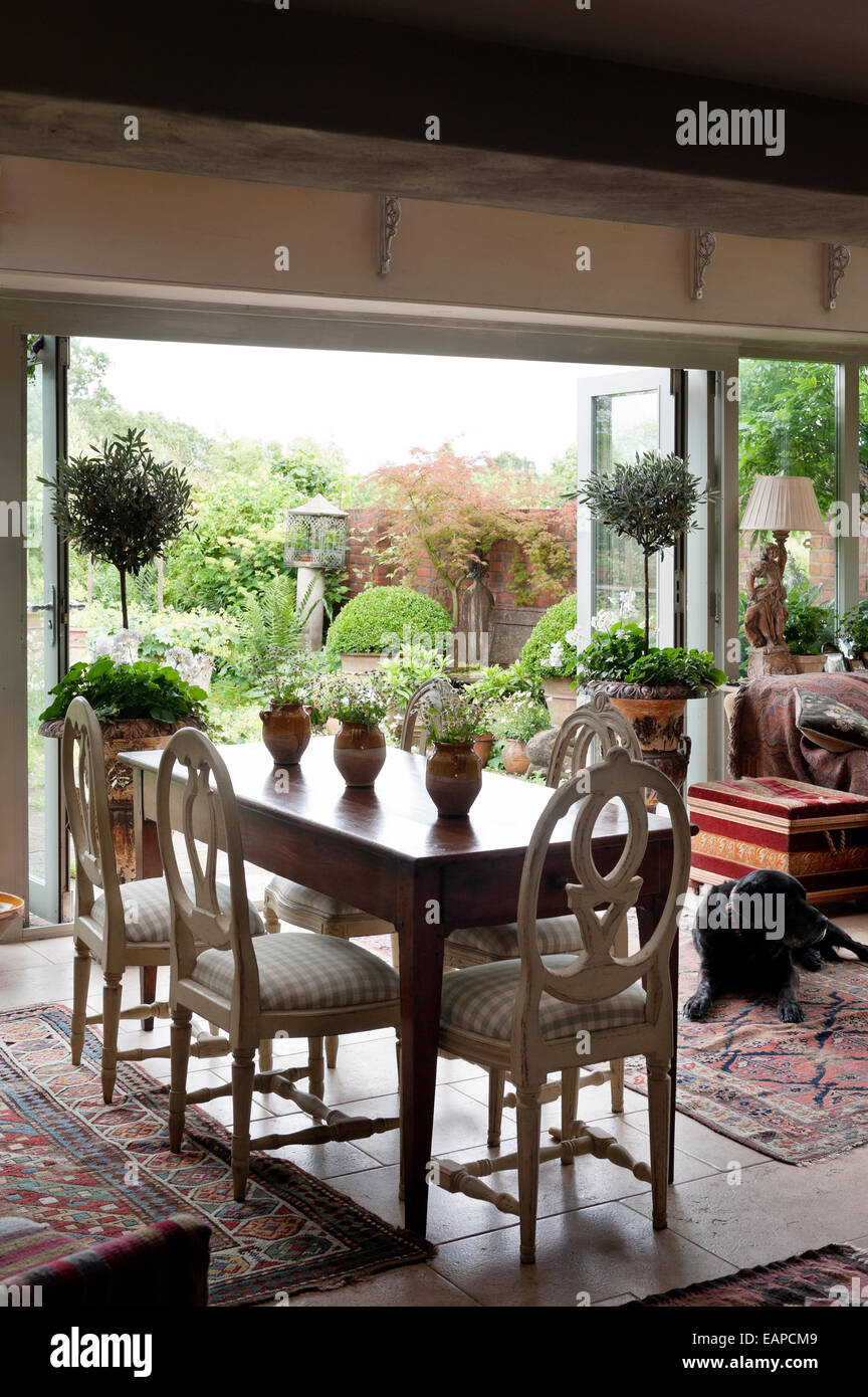 Roundback Wooden Dining Chairs Around Antique Farmhouse Table In Room With Open French Windows Leading Out To Garden