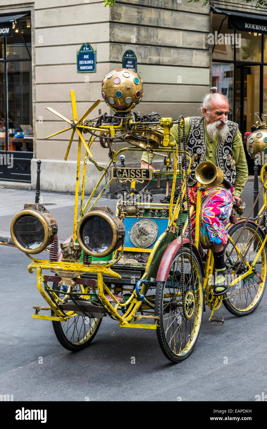 man in multi colored attire on kinetic bicycle construction, paris, ile de france, france - Stock Image