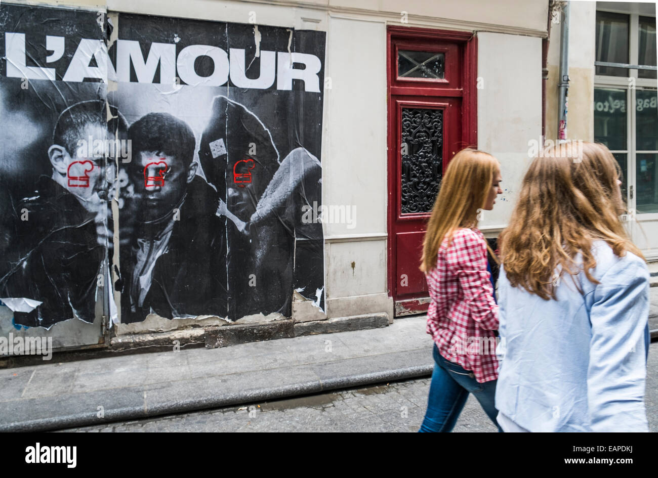 two young women passing by a poster on a wall showing three youth one of them holding a gun, the lettering on top - Stock Image
