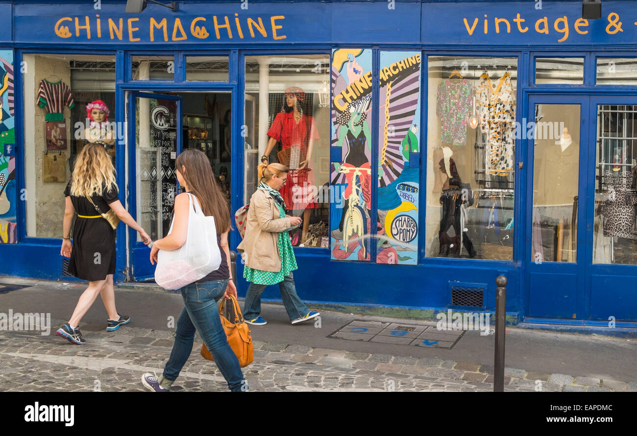 female passer byes  in front of chine machine vintage fashion store in the montmartre district, rue des martyrs, - Stock Image