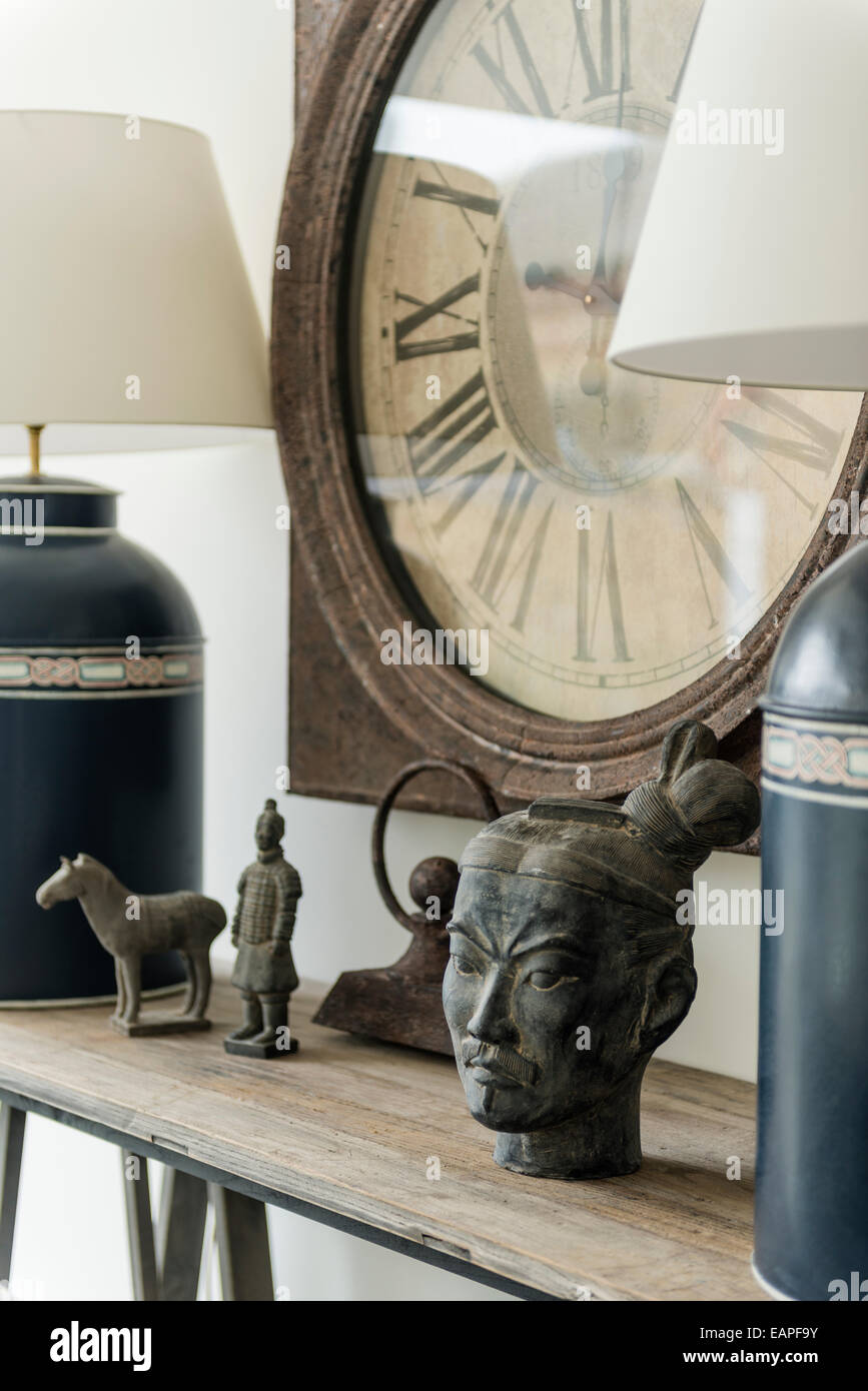 Detail of Chinese antiquities and tea canister lamps on wooden ledge with Old Clock on wall behind - Stock Image