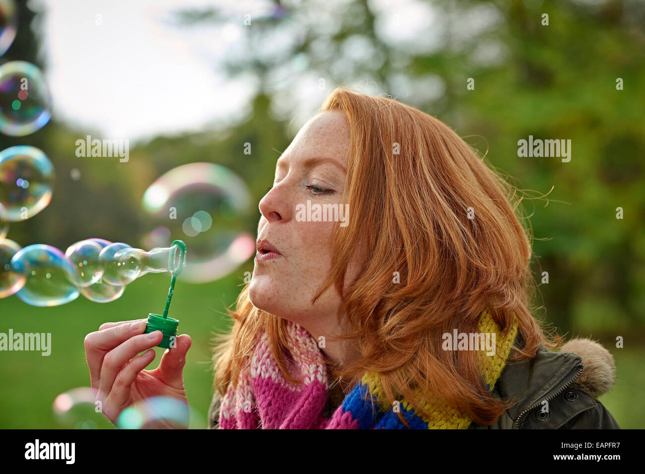 Woman blowing rainbow bubbles - Stock Image