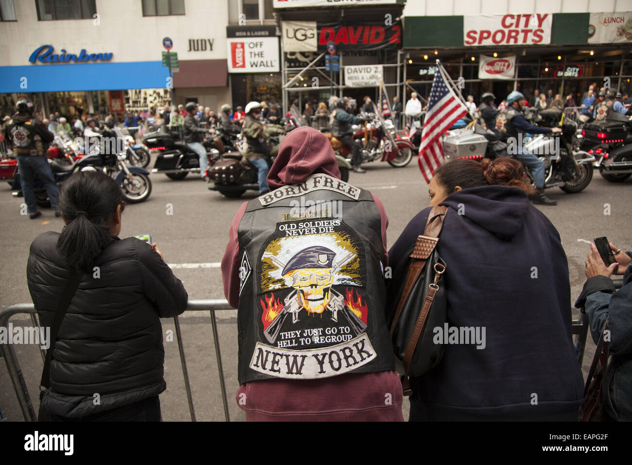 Veterans Day Parade, 5th Ave., New York City. Military vet watches as motorcyclist vets pass by. - Stock Image