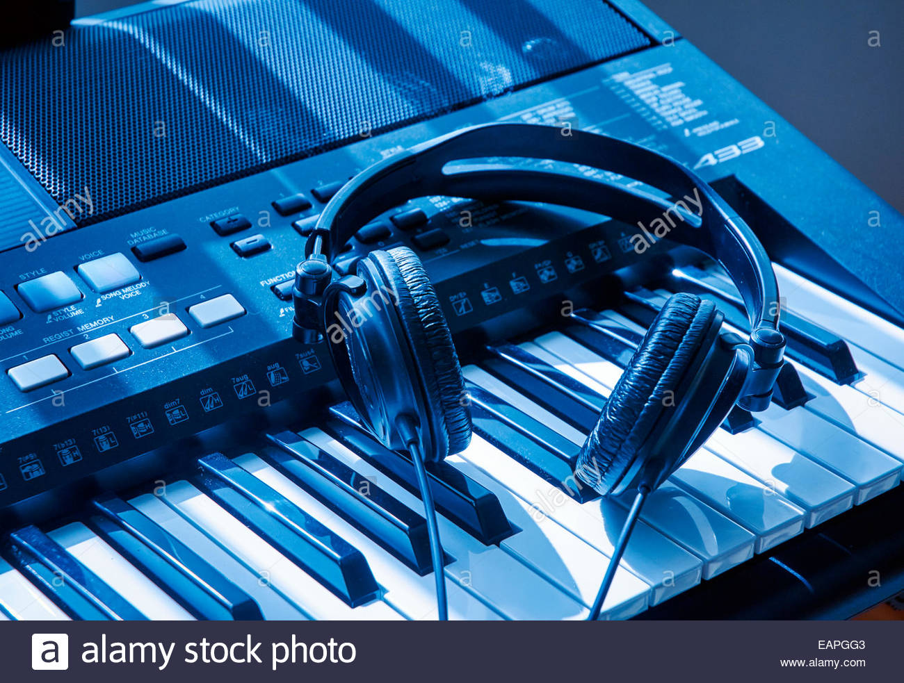 electronic keyboard synthesizer and headphones with black and white keys tinted blue - Stock Image