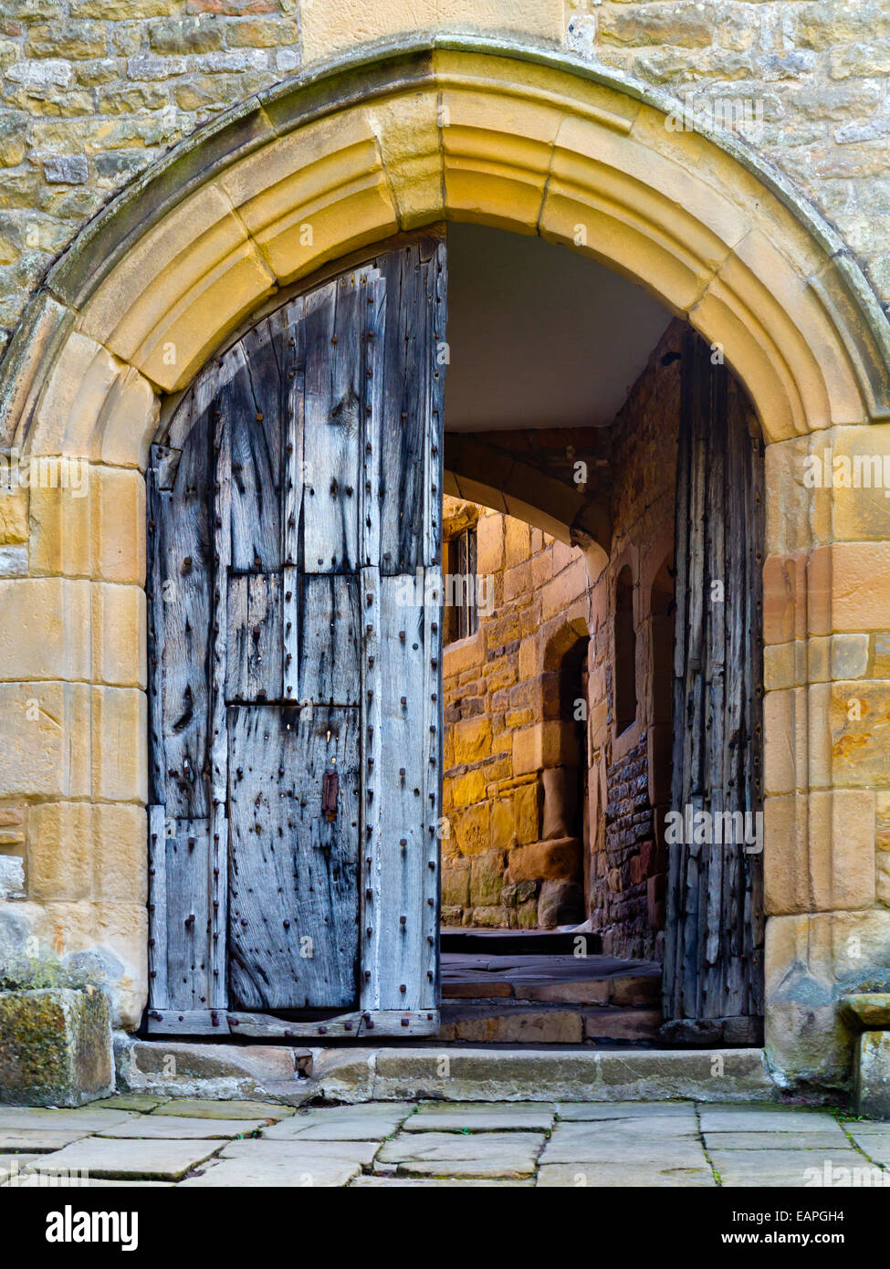 Wooden entrance door and archway into the inner courtyard at Haddon Hall near Bakewell Peak District National Park Derbyshire UK & Wooden entrance door and archway into the inner courtyard at Haddon ...