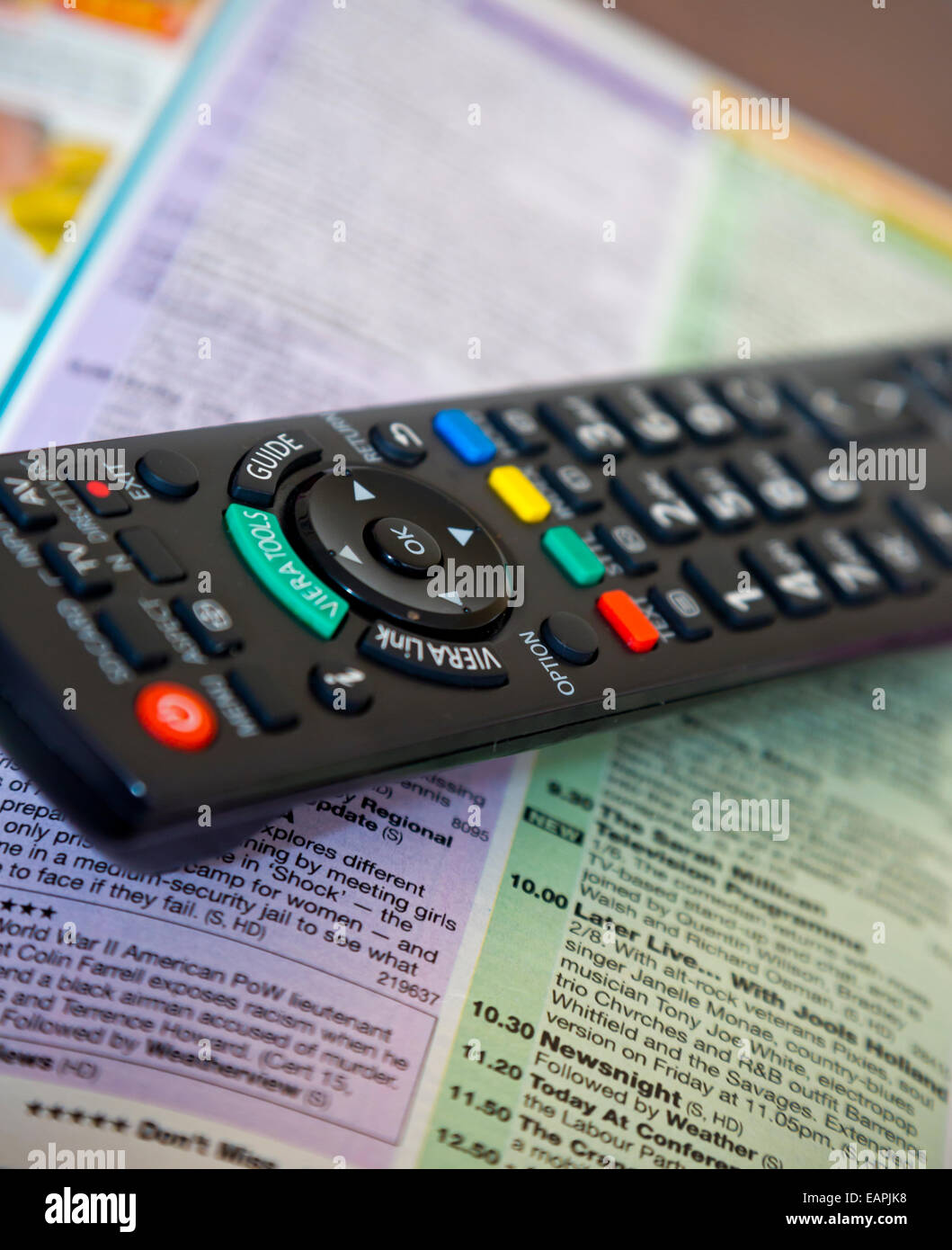 Television remote control handset resting on a tv listings guide - Stock Image