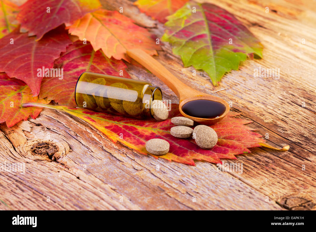 medicine bottle, pills on leaf and syrup in wooden spoon on wooden background - Stock Image