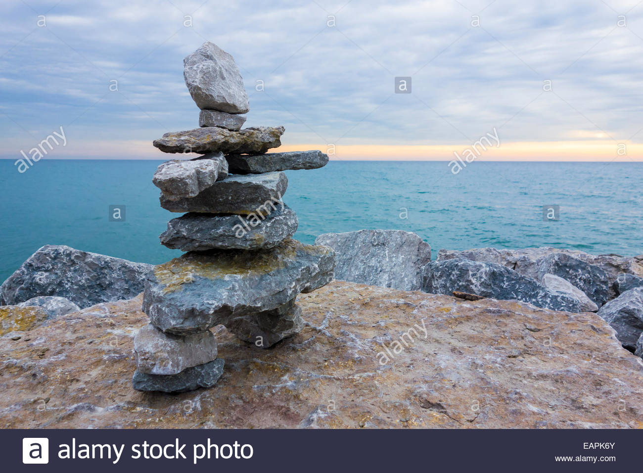 A Small Inukshuk A Stone Cairn And A Canadian Symbol Beside Lake