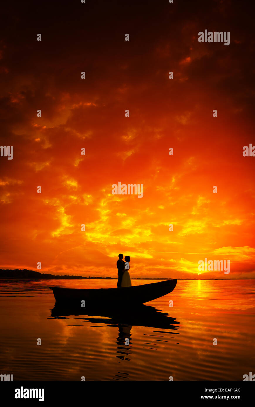 Silhouette of a couple in boat on river in sunset, beautiful skyes - Stock Image