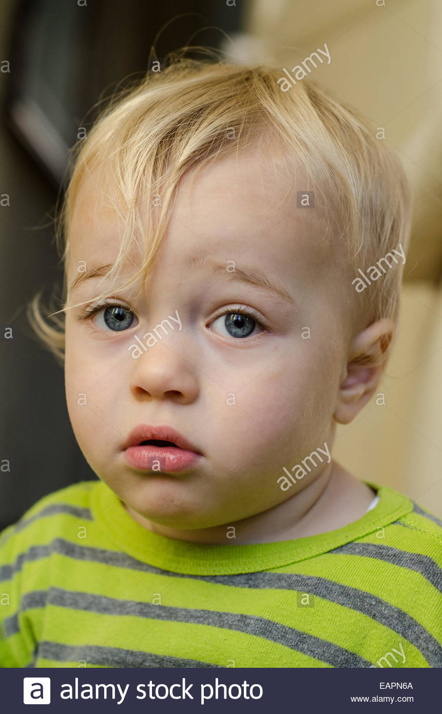 Portrait of a blond blue eyed 18 month old boy wearing a stripy jumper