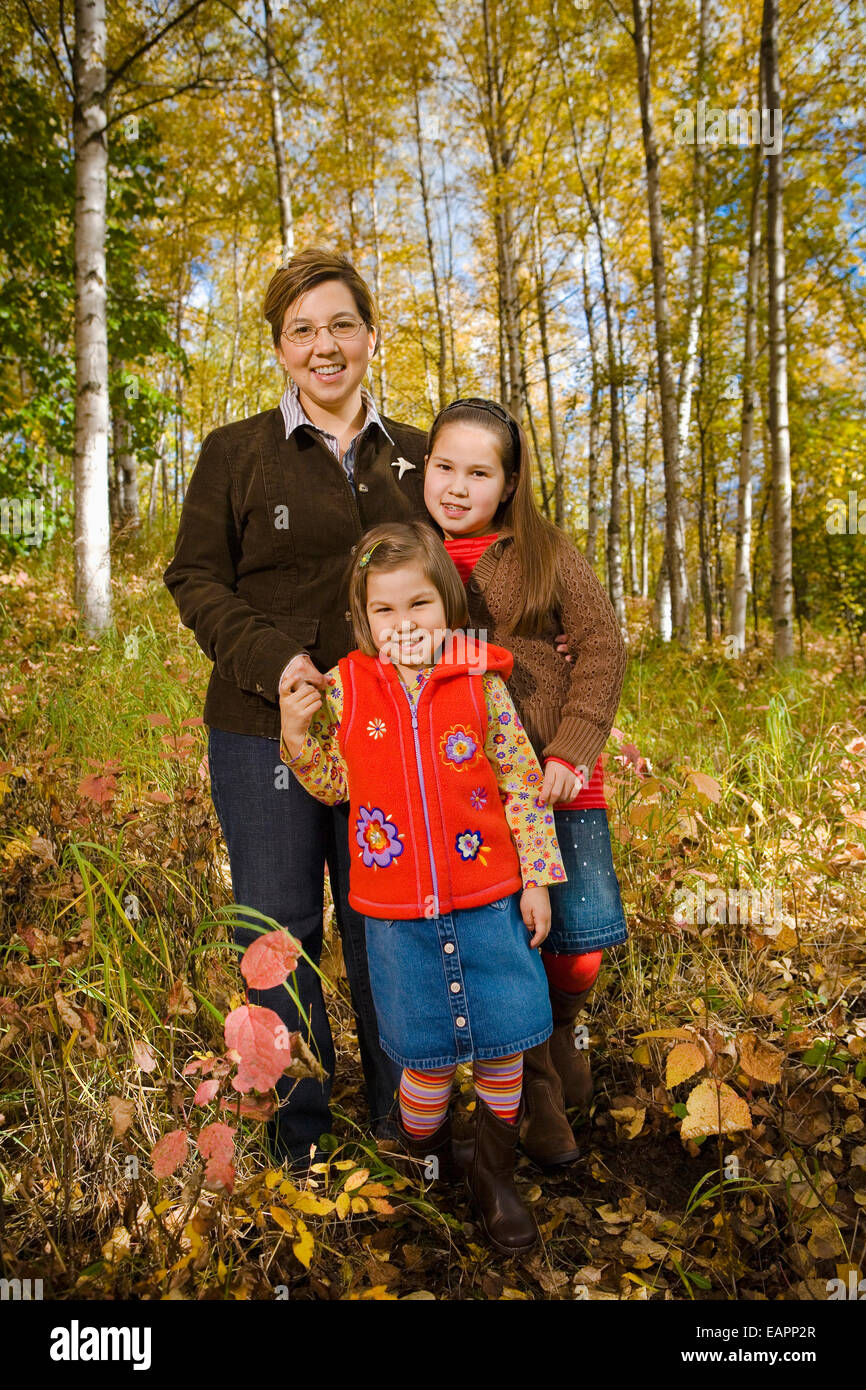 Native Family Standing In Birch Forest During Fall In Southcentral, Alaska - Stock Image