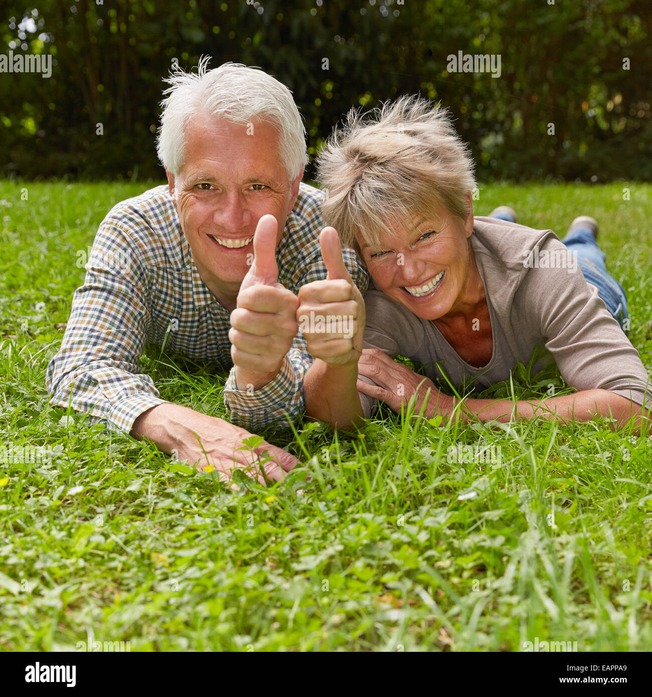 Happy senior couple holding two thumbs up for congratulation - Stock Image