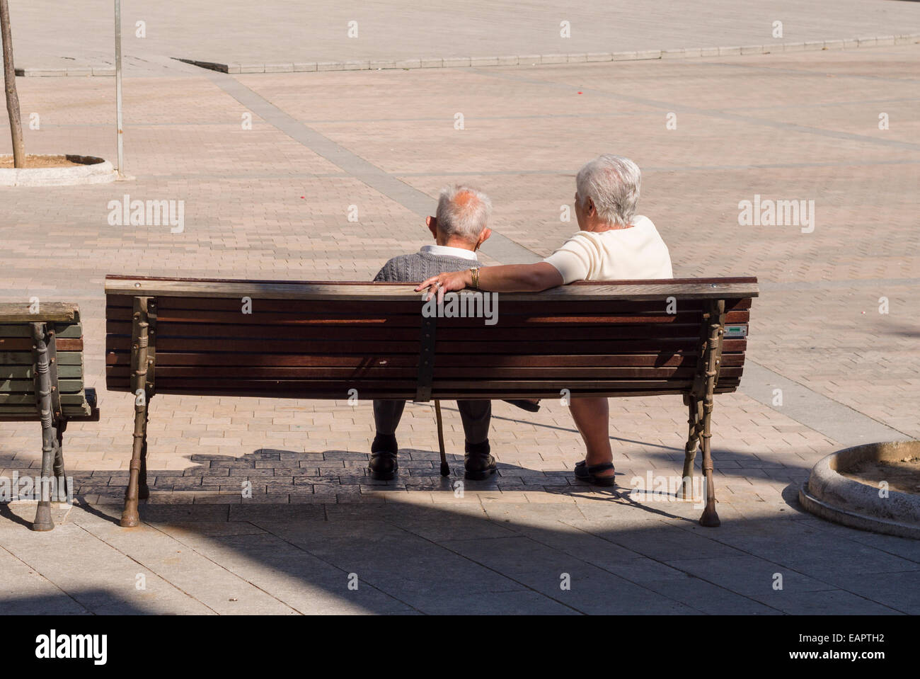 Taking a Rest Break on a bench. A older couple with white hair take a break on a bench in the central square of - Stock Image