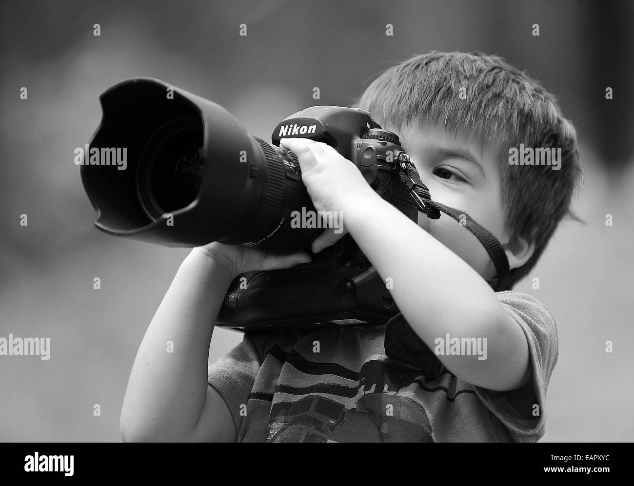A young 3yr old boy trying out his dads Nikon D3 professional camera while out on a family walk in Melbourne, Australia. - Stock Image