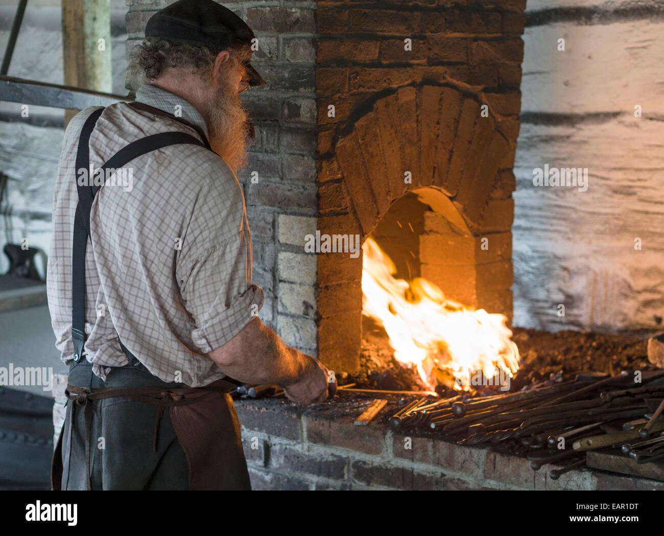 Blacksmith at his forge. A blacksmith heats the iron with his right hand while pumping the bellows with his left. - Stock Image