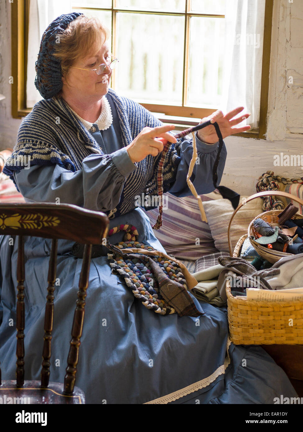 Making a Rag Rug: domestic labour. A woman in costume picks out the next element in her rag rug. - Stock Image
