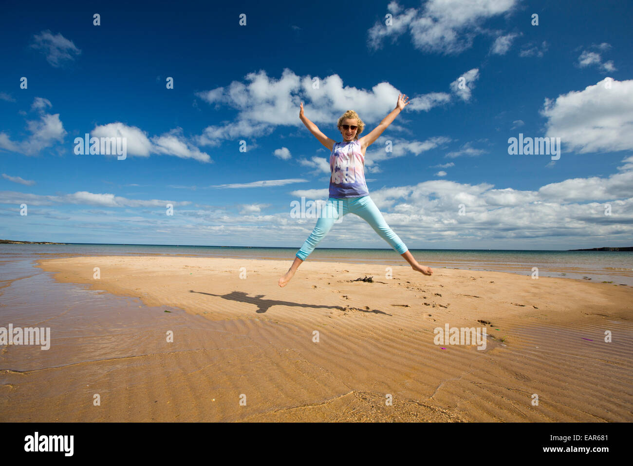 A teeneage girl on a sandy island being cut off by the incoming tide at Low Newton, Northumberland, UK. - Stock Image