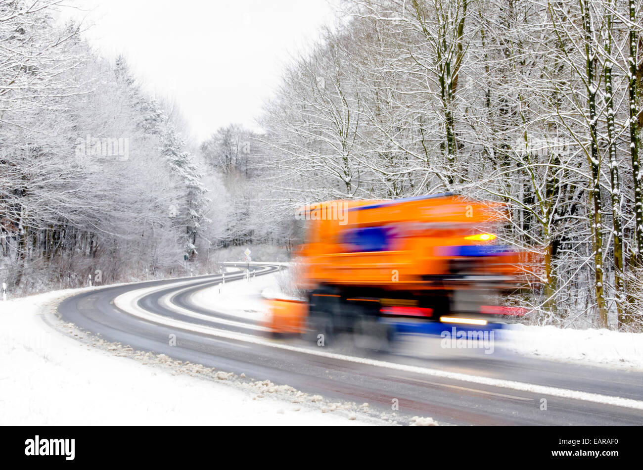 Snowplow working on icy winter road, vehicle blurred - Stock Image