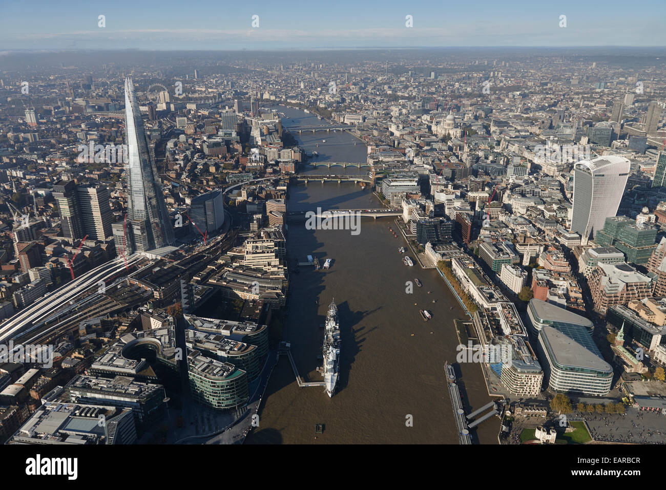 An aerial view looking down the River Thames with HMS Belfast in the foreground and the Shard visible - Stock Image
